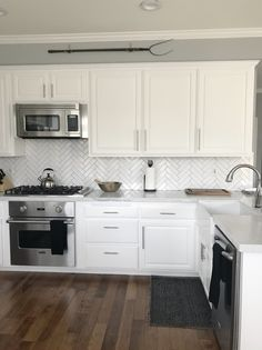 White cabinets with white Carrera Marble farm house sink and white chevron subway tile with & white cabinets with black/oil-rubbed-bronze hardware and a white ...