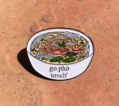 DESCRIPTION:  This is a nickel-plated enamel pin that is 1 1/8 in size with a black rubber clutch. Original design of a bowl of phở with the suggestion