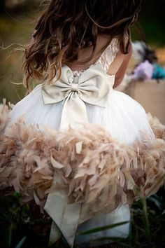 What a beautiful flower girl dress. I am sure that this could be achieved by sewing or gluing on a feather boa.