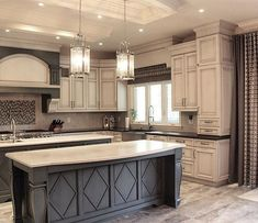 Dark grey island with white countertop and antique white cabinets with black count