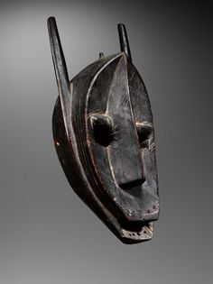 exhibitor of Suruku hyena mask Hardwood with ancient brown-black patina and red highlights Bamana culture, Koulikoro region, Mali Dated 19th century H 53 cm This mask is striking not only because of its size, but also because of the vigorous yet knowing features of the concave face and its superb patina. It would have been used to impress the audience at secret Koré ceremonies. The hyena symbolizes the effort young men must make to improve their knowledge Provenance: J.J. Klejman, New York…
