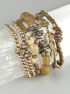 Collection of 5 Ritual bracelets from Ann Lambrecht Jewelry which include: Brass Ethiopian wedding rings, copper freshwater pearls (symbolize purity), brass fertility symbols from Nepal, vintage glass beads from Ghana, brass trade beads from Africa, and diamond quartz (used to amplify both body energy and thoughts).