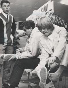 Rolling Stone Brian Jones, adjusting his shoe before hitting the stage.