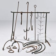 Group of Wrought Iron Hearth HardwareGroup of Wrought Iron Hearth Hardware, America, late 18th/early 19th century, including a hanging rack, twelve pot lifters, three hooks, a large skewer, two game hooks and smoking rack, lg. to 40 in.  Estimate $200-400