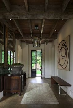 rustic foyer entrace design with exposed wood beams, black indoor lantern, modern walnut skinny bench, travertine floor, black glass french doors, vintage mirror and credenza.
