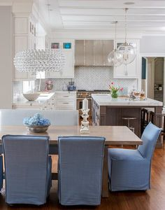 Open plan dining room positioned beside a white kitchen is fitted with a Bulle Pendant hung over a caramel stained x-based dining table surrounded by blue slip covered dining chairs and a dove gray dining bench.