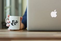 Free PSD Photorealistic In Hand Coffee Cup Mockup with Apple Macbook Pro