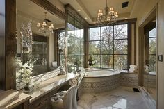 Large windows, glass shower door & lots of large mirrors make this fairly narrow bathroom feel large.