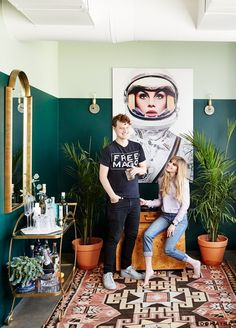 Carlson Young in her eclectic living room with two-tone forest green walls, a large astronaut print, a large gold mirror, and a rug