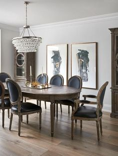 Side by side black and gold abstract art piece hang on a white wall between tall glass cabinets and behind an oval French dining table surrounded by black leather round back French dining chairs lit by a Robert Abbey Oval Bling Chandelier.
