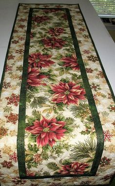 Poinsettia Table Runner, handmade, quilted, fabric Robert Kaufman Holiday Flourish Measures 48 x 14.5 inches Made by Chris This gorgeous fabric has rose colored poinsettias, holly and berries. It has beautiful rich mauve/rose poinsettias and dazzling green foliage with lots of metallic gold to add shimmer. The accent fabric is a lovely green with metallic from Hoffman. The outside border is full of beautiful metallic rose/mauve, green and gold snowflakes and is also from Robert Kau...