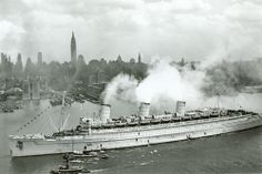 Tugboats escort the stately British former ocean liner Queen Mary as she steams into New York Harbor on June 20, 1945, still wearing her ocean-gray camouflage and bringing thousands of veterans home from the war in Europe. Families and the press wait dockside in Manhattan to give the boys a rousing homecoming. (National Archives)