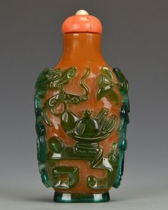 """Green and Amber Colored Peking Glass Snuff Bottle, Qing dynasty, the amber colored bottle with green glass carved overlay to depict the """"hundred antiquities"""" on the front and back along with a chilong dragon, on a green oval foot ring, topped with a coral and pearl stopper with bone spoon, approx. 7 by 3 cm, 2 3/4 by 1 1/4 in."""