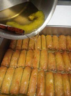 Υλικά συνταγής: μισό κιλό φύλλο κρουστάς 200 γραμ. φρέσκοβούτυρο για το σιρόπι: 500 γραμ. ζάχαρη 400 γραμ. νερό ξυλάκι κανέλα φλούδα από λεμόνι λίγο χυμό λεμόνι Γέμιση: 100 γραμ. καρύδια 100 γραμ. αμύγδαλο 60 γραμ. σουσάμι 160 γραμ. ζάχαρη 80 γραμ. φρυγανιά η μπισκότο 2 αυγά 30 γραμ. ανθόνερο 10 γραμ. κανέλα Εκτέλεση: Βάζουμε το … Greek Sweets, Sausage, Recipies, Food And Drink, Cooking Recipes, Meat, Baking, Xmas Cakes, Laura Ashley
