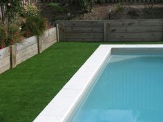 Artificial turf up to pool coping with short wooden retaining wall - pretty much the formula.  Need a few twists to make it interesting.