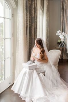 bride opens gift from groom on wedding day in bridal suite of Park Chateau Estate   Elegant summer wedding at Park Chateau Estate with ivory and pastel details photographed by New Jersey wedding photographer Idalia Photography. Planning a Park Chateau Estate wedding? Find inspiration here! #IdaliaPhotography #ParkChateauEstate #SummerWedding