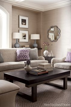 A niche lends depth to the family room, where the neutral color scheme punctuated with purple continues.