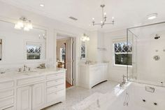 East Hampton's Historic George Osborne House small tile flooring, white cabinetry, decorative window mullions, a glass enclosed shower, marble countertops, dual vanities, and hanging light fixtures.
