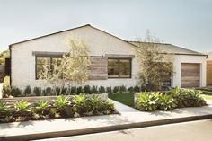 Ranch style exterior-modern farmhouse details. Weather wood shutters on barn door rails and garage doors. Stucco. Eric Olson design.