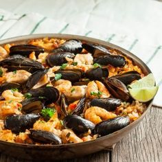 Easy Seafood Paella Recipe Main Dishes with chicken broth, clam juice, whitefish, mussels, clams, extra large shrimp, kosher salt, freshly ground black pepper, salted butter, onions, garlic, chopped cilantro, basil, scallions, smoked paprika, roma tomatoes, arborio rice, lemon wedges