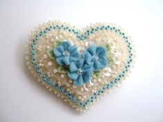 Hi!    This sweet heart pin is made entirely of 100% wool felt.  Lots of pretty beading, vintage AB sequins, dainty felt flowers and a few Swarovsky