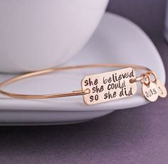 "A 14k gold filled rectangle measuring 1 1/8 of an inch across is engraved with the words ""she believed she could so she did"". The bracelet band and charms are 14k gold filled. Each bangle is hand form"