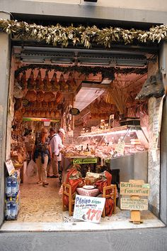 Italian Butcher Shop. See all the hanging cured hams, but especially the wild boar head on the right hand wall ! Very cool.