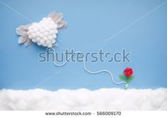 Flying white heart with feather wings, attached by a white string to a tiny handmade red flower, in a heavenly scenery with clouds made of cotton-wool, on a blue sky paper background.