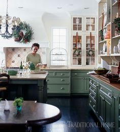 This green Country French kitchen opens up to the great room, where guests can sit in comfort and visit with the homeowner. - Photo: Colleen Duffley / Design: Gretchen Edwards
