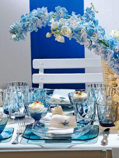 È tutta mediterranea la tavola che Enzo Miccio ha scelto di dedicare al mare: il blu è il colore dominante, che troviamo non solo nei pezzi di arredo, ma anche nei fiori e nel background, che ci porta immediatamente con l'immaginario alle spiagge toscane, con i loro ombrelloni colorati, i pattini e le discoteche sulla spiaggia.