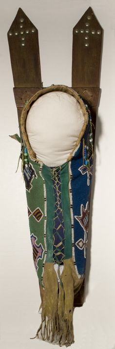 Fully Beaded Lattice Cradle (pajop),  late 19th c.  Kiowa peoples, Southern Plains, Oklahoma  Glass beads, tanned deer skin, canvas, cotton cloth, wood, German silver tacks, raw-hide, pigment, 43.75 x 13.75 x 10.25 inches    courtesy U of Virginia Art Museum