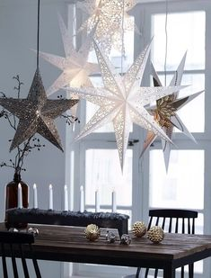 Dining area with Christmas decoration in natural colors, big paper stars, lit up, hanging from ceiling, Scandivanvian