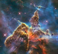 Mystic Mountain , in Carina Nebula, located 7500 light-years away in the southern constellation of Carina. Nestled inside this dense mountain are fledgling stars. Long streamers of gas can be seen shooting in opposite directions from the pedestal at the top of the image. Another pair of jets is visible at another peak near the centre of the image.