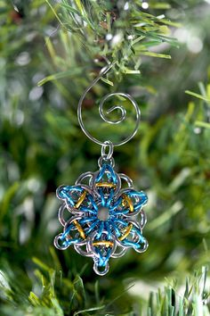 Decorate your Christmas tree with this lovely and unique chainmaille snowflake ornament. Made from hardy 18 gauge stainless steel and 18 gauge turquoise and gold anodized aluminum, this snowflake is not one that will melt away -- it can be handed down to generations to come. The