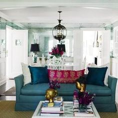 Refinery 29 - living rooms - columns, wainscoting, mirror paneled walls, antiqued mirror paneled walls, antique mirror panel walls, hardwood floors, dark hardwood floors, white dining table, white dining chair, white chippendale dining chair, orb shaped chandelier, iron orb shaped chandelier, sphere shaped chandelier, iron sphere shaped chandelier, blue sofa, blue skirted sofa, peacock blue pillow, peacock blue silk pillow, white pillow, fuchsia pink paisley pillow, pink paisley pillow, ...