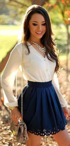 Dark blue skater skirt with cut out detail and loose white long-sleeved blouse