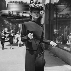 Manhattan, September 1945    NBC network engineer and Glamour girl of the month, Katharine Reynolds, on the street in front of work wearing a suit with a pitched forward hat and carrying a drawstring handbag.