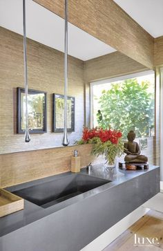 An unusually spacious powder room with a wall of windows overlooking the garden gives guests a mini-spa to retreat to during dinner parties. Fragali custom-designed the oversize quartz sink. A waterdrop-style Gessi faucet floats down from the ceiling, and a Ralph Lauren Home wallcovering from Wall Boutique envelops the space in warmth.