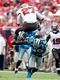 Tampa Bay Buccaneers running back LeGarrett Blount jumps over the tackle of Carolina Panthers safety Charles Godfrey.