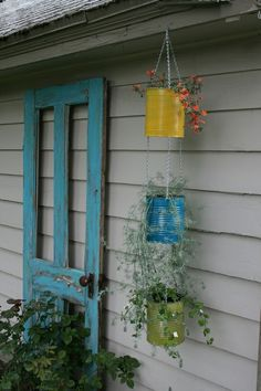 Tin can vertical plant hanger and rustic painted wooden screen door.  Love the screen door as a decorative element with potted plants surrounding. Old paint cans?