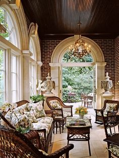 Conservatory with brick wall a porcelain-and-gilt chandelier and beautiful arched windows.