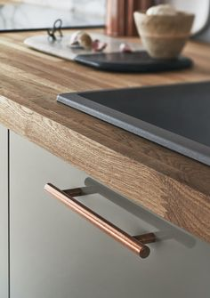 Howdens A Solid Rustic Oak Worktop complements a Gloss Grey kitchen beautifully, and the look is completed by copper handles. Find out more at Howdens. Rustic Kitchen Cabinets, Kitchen Cabinet Doors, Kitchen Handles, Kitchen Cabinet Design, Kitchen Furniture, Kitchen Interior, New Kitchen, Kitchen Wood, Wood Cabinets