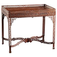 """A Chippendale fretwork tea/silver table in mahogany. Featured in """"Masterpiece of Queen Anne & Georgian Furniture"""" my F. Lewis Hinckley, pg. 85, pl. 134. This exuberant example displays a fretwork laminated gallery with figural top over a mirror image frieze with blind fretwork. The legs are fretworked as well with carved edges & joined by an undulating cross stretcher with piercing as well. English or Irish, circa 1770. L: 34.5"""" D: 23.25"""" H: 29.5""""   G. Sergeant Antiques L.L.C., Woodbury, CT"""