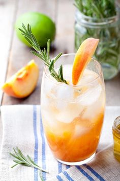 Eastern Shore Honey Vodka with peach and rosemary garnish on blue striped napkin on top of table.
