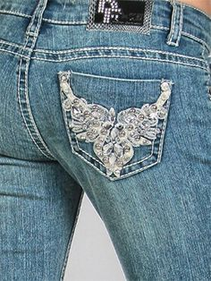 """Stockyard Style is proud to carry a new line of rhinestone bling jeans by design fusion, or """"D-Fuz."""" This high quality denim product is comfortable, and most importantly, stylish!    Jeans run true to size. Slightly longer than standard inseams are perfect for wearing with boots. """"Leather Wings"""" features a blue wash stretch denim with bold white stitching. The back pockets feature a white leather wing design with lots of rhinestone details.  The front also features a large rhinestone button…"""