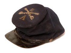 """Union Model 1858 Forage Cap, aka Bummer's Cap. Fine condition with flat visor, 1/8"""" thickness. No apparent mothing. Fabric is fine wool and very dark blue with no fading. The crown of the cap is adorned with crossed sabers and regimental and company devices which are correct Civil War issue but added to the hat. The tarred leather chinstrap which terminates at two eagle buttons is original with a black leather bill firmly attached to cap. 100% of the polished cotton lining remains and the…"""