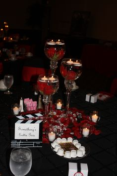 Red Black White Weddng. Movie Theme.  Used clapbroads for table names.  Got candle holders from Bed and Bath.  Used silk roses, but wanted them to sink so I hot glued fishing sinkers in them.  Worked great.  Also a tip, rinse off the flowers a couple of times to remove the dye or your water will turn red.