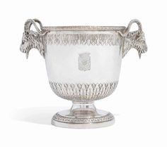 A GERMAN SILVER WINE-COOLER MARK OF JOHANN JAKOB HERMANN GRABE, AUGSBURG, 1800 Cylindrical, chased with leafage with ram's mask side handles, engraved with coat of arms, marked underneath, engraved '#3' and with scratchweight '4 90 30' 9 1/8 in. (23.2 cm. high) 64 oz. 9 dwt. (2,005 gr.) The arms are those of Stroganoff, for Count Alexander Stroganoff (1733-1811).