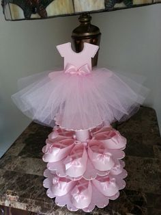 This unique centerpiece is perfect if youre looking for both shower favors and a centerpiece for your upcoming ballerina baby shower event. The stand has two tiers that can hold 15 pink shoe favors (included) if you need more shoes check out our listing for just the shoe favors. They come in a set of ten. Height of the stand with the dress topper is about 15 inches. the widest diameter of the stand at the bottom is 11 inches. Each shoe measures 3.5 inches in length. Fill them with delicious…