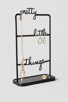 """Organize in style with the Pretty Little Things Jewelry Stand! This metal stand with tray lets your display all your pretty little things. Pair with our additional home decor options for a complete look.<br /> <br /> - 16"""" height<br /> - 9"""" length<br /> - By Umbra<br /> - Imported"""